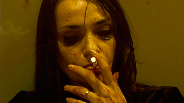 Beatrice Dalle's La Femme takes a cigarette break before she invokes more vengeance. INSIDE, Alexandre Bustillo &  Julien Maury Cinematography | Laurent Barès