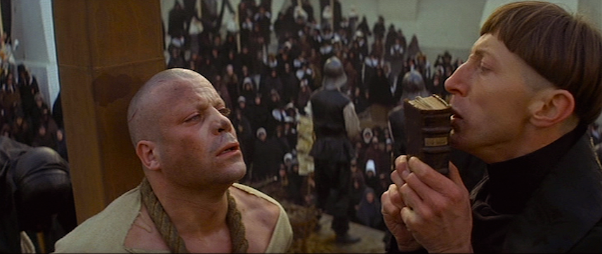 A fellow priest begs Granier to confess and be spared. He refuses. The guilt-ridden priest seems to be praying more for himself than Granier.  Oliver Reed / Murray Melvin The Devils Ken Russell, 1971 Cinematography | David Watkin