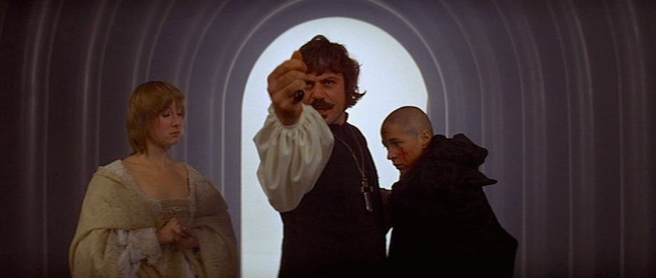"Oliver Reed as Father Urbain Grandier. While presented as a man of faith and ethics, he is also a cruel and callous man who is more than happy to seduce the females of his flock. The line between good and evil is a thin one for this ""progressive"" priest.  The Devils Ken Russell, 1971 Cinematography 